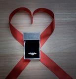 Anneau de mariage et ruban rouge de coeur sur la surface en bois Photo libre de droits