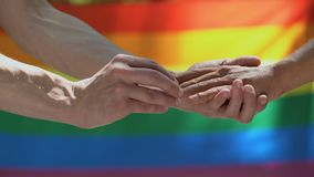Anneau de mariage de mise masculin homosexuel sur l'associé, fond de drapeau de lgbt, égalité banque de vidéos