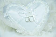 Anneau de mariage sur l'oreiller blanc et le fond mou de tissu Photo libre de droits