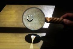 Anneau de mariage sur un fond et une loupe en bois Image stock