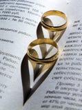 Anneau de mariage sur un livre avec une ombre dans la forme Photos stock