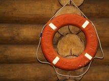 Anneau de vie orange accrochant sur une barrière brune en bois photo libre de droits