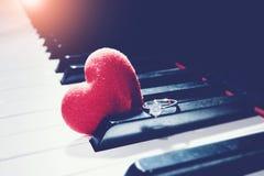 Anneau et coeurs sur le piano, ton de vintage Fond de jour de valentines photo stock