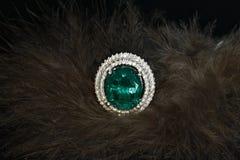 Anneau vert avec des diamants sur le fond de plumes Photo libre de droits