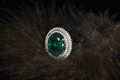 Anneau vert avec des diamants sur le fond de plumes Images stock