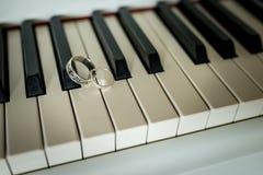 Anneaux argentés de mariage se trouvant sur les clés de piano photographie stock libre de droits