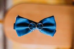 Anneaux bleus de noeud papillon et de mariage sur le fond en bois Photo stock
