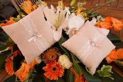 Anneaux d'or avec des diamants sur le coussin blanc près de l'orange de bouquet de mariage pour la jeune mariée photo stock