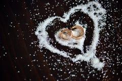 Anneaux d'or de mariage au coeur de sucre sur le fond en bois foncé Photographie stock libre de droits