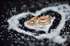 Anneaux d'or de mariage au coeur de sucre sur le fond en bois foncé Photos libres de droits