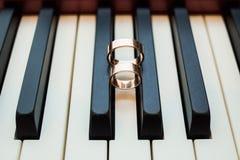 Anneaux d'or de mariage brillant sur des clés noires et blanches de piano Image libre de droits
