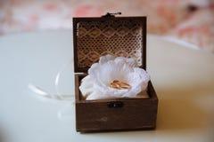 Anneaux d'or de mariage dans une boîte en bois sur le fond blanc Concept de l'amour Image libre de droits