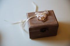 Anneaux d'or de mariage dans une boîte en bois sur le fond blanc Concept de l'amour Photos libres de droits