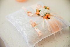 Anneaux d'or de mariage sur la lumière de coussin Photo stock