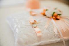 Anneaux d'or de mariage sur la lumière de coussin Photo libre de droits
