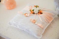 Anneaux d'or de mariage sur la lumière de coussin Photos stock