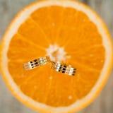 Anneaux d'or de mariage sur le fruit orange Photos libres de droits