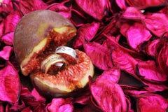 Anneaux d'or et d'argent de mariage dans la figue, concept d'amour Photo libre de droits