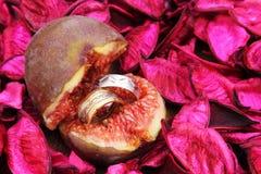 Anneaux d'or et d'argent de mariage dans la figue, concept d'amour Photos stock