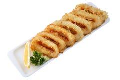 Anneaux d'oignon frits par four, pâte lisse plongée, dans une rangée Images libres de droits