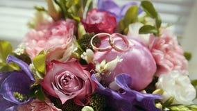 Anneaux d'or sur le bouquet coloré de mariage banque de vidéos