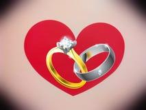 Anneaux de bijoux sur un fond des coeurs Photographie stock libre de droits