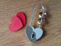 Anneaux de mariage à la serrure et à deux coeurs rouges Photo libre de droits