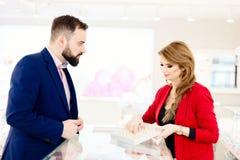 Anneaux de mariage de achat d'homme dans le magasin de bijoux Photos stock