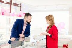 Anneaux de mariage de achat d'homme dans le magasin de bijoux Image libre de droits