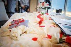 Anneaux de mariage ainsi que la corde rouge sur l'oreiller rayé avec l'anch Photo stock