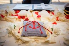 Anneaux de mariage ainsi que la corde rouge sur l'oreiller rayé avec l'ancre là-dessus Cérémonie de mariage Image stock