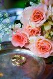 Anneaux de mariage avant la cérémonie, avec les verres de Champagne et les roses décorés Image stock