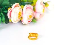 Anneaux de mariage avec des fleurs sur le blanc Images stock
