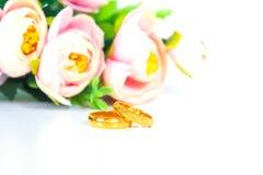 Anneaux de mariage avec des fleurs sur le blanc Photos stock