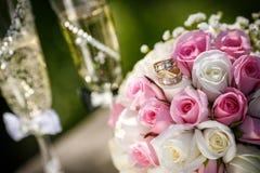 Anneaux de mariage avec des roses et des verres de champagne Photographie stock