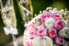 Anneaux de mariage avec des roses et des verres de champagne Photo stock