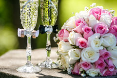 Anneaux de mariage avec des roses et des verres de champagne Image stock