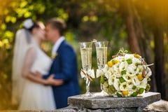 Anneaux de mariage avec des roses et des verres de champagne et d'un baiser du marié et de la jeune mariée Photo stock