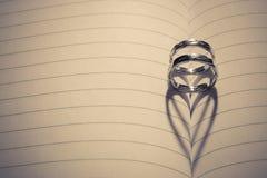 Anneaux de mariage avec l'ombre de forme de coeur sur le papier Photos libres de droits