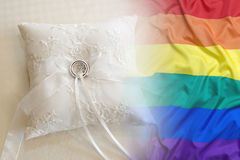 Anneaux de mariage avec le drapeau d'arc-en-ciel sur un oreiller Photographie stock