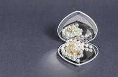 Anneaux de mariage avec le fond de gris de décoration de bijoux Photographie stock