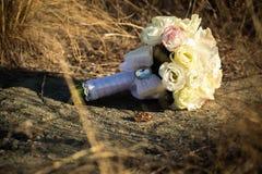 Anneaux de mariage avec un bouquet des roses Se situer dans la rue Photos stock