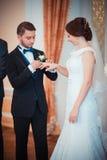 Anneaux de mariage d'échange de jeunes mariés Photo libre de droits