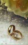 Anneaux de mariage d'or avec un bouquet nuptiale photographie stock libre de droits