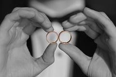 Anneaux de mariage d'or dans des mains Photos libres de droits