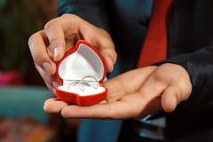 Anneaux de mariage d'or dans des mains du marié Photo libre de droits