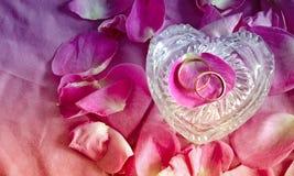 Anneaux de mariage d'or dans une boîte en verre sous forme de coeur et de pétales de roses roses Fond de mariage Photos libres de droits