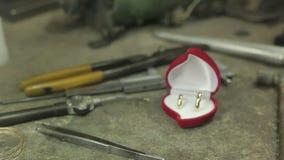 Anneaux de mariage d'or dans une boîte rouge, sur le bureau clips vidéos