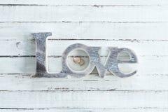 Anneaux de mariage d'or et symbole d'amour sur le dessus de table en bois Photographie stock libre de droits