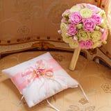 Anneaux de mariage d'or et un bouquet de la jeune mariée Roses roses et blanches Coussin décoratif de satin pour les anneaux photo stock